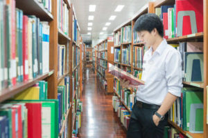 38742727-asian-student-in-uniform-reading-in-the-library-at-university